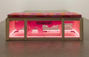 <i>gun bench (code pink protest props in support of march for our lives,</br>remembering marjory stonemason douglas high school), 2018</br>reused wood, plexiglass, neon, cardboard, acrylic paint, cushion</br> 59,7 x 182,9 x 61 cm / 23.5 x 72 x 24 in