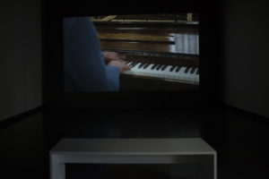 <i>partition pour mains et masse</i>, 2018 </br> full hd video, sound thanks to: john mcghee (composition and interpretation) and sylvian croci-torti (jack hammer) </br> 15'17'' </br> installation view, kiosk, ghent