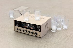 <I>Background</I>, 2019 </br> shortwave radio receiver, coagulated air, drinking glasses </br> variable dimensions, installation above: 26 x 105 x 56 cm / 10.2 x 59 x 9 in